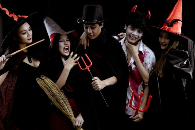Grupa młodych azjatów w kostiumach halloween na czarnej ścianie z koncepcją na halloweenowy festiwal mody.