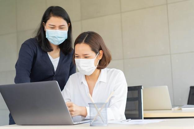 Grupa młodych azjatyckich kobiet pracowników konsultacji na komputerze stacjonarnym i wpisz na klawiaturze laptopa