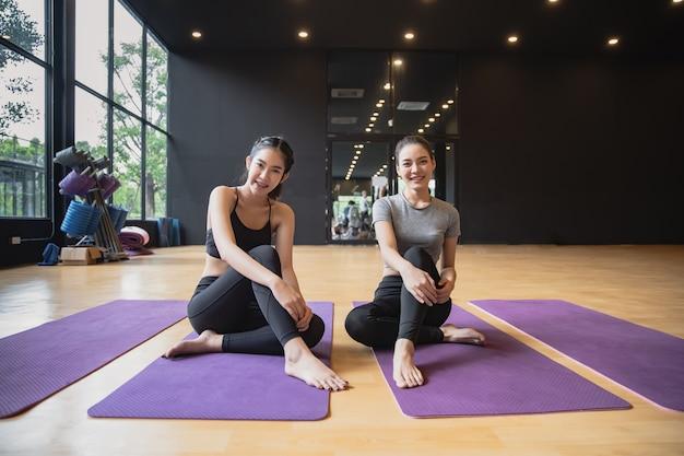 Grupa młodych azjatyckich kobiet sportowy siedzieć na matach do jogi, uśmiechając się i rozmawiając po ćwiczeniu jogi