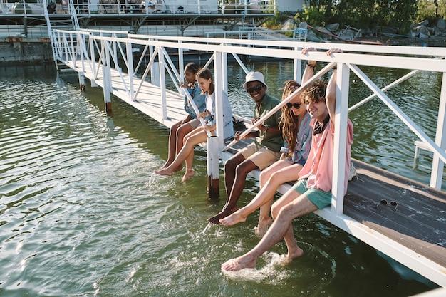 Grupa młodych beztroskich przyjaciół relaksujących się na moście i pluskającej się wody