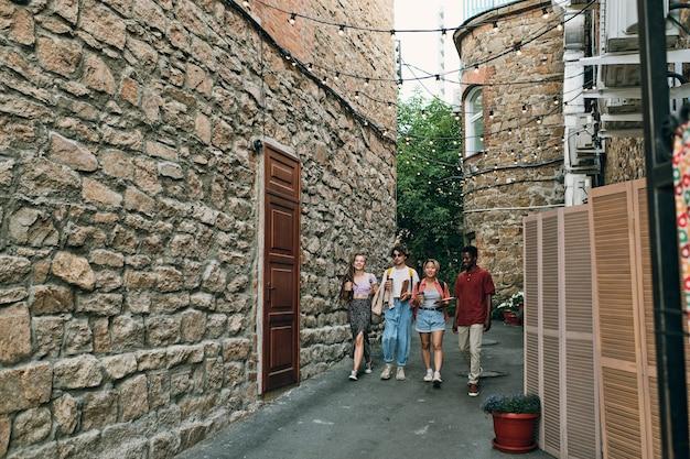 Grupa młodych beztroskich przyjaciół z napojami poruszającymi się wąską drogą między budynkami