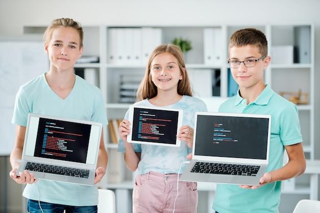 Grupa młodych chłopców i dziewczyn trzymających laptopy i touchpad, pokazując swoje ostatnie prace na koniec roku szkolnego