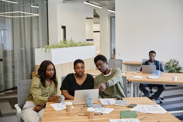 Grupa młodych czarnych ludzi biznesu oglądających prezentację produktu na ekranie laptopa na spotkaniu