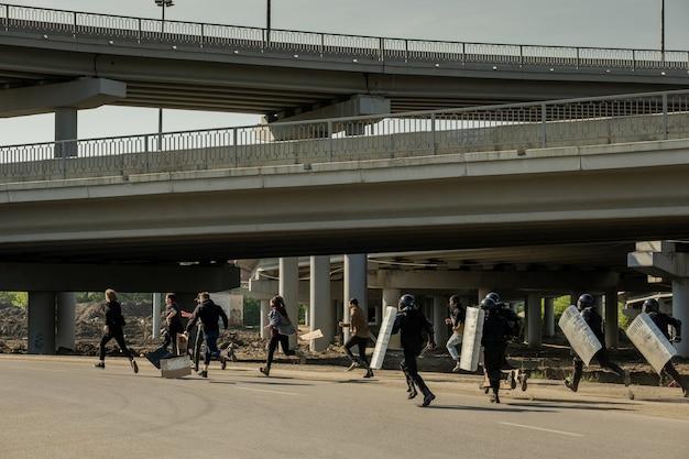 Grupa młodych demonstrantów z tablicami biegnącymi przed policją po nieautoryzowanym wiecu, rozproszona przez funkcjonariuszy