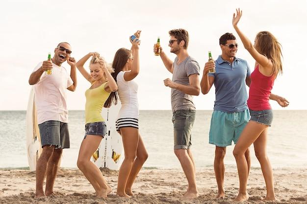 Grupa młodych dorosłych imprezujących na plaży