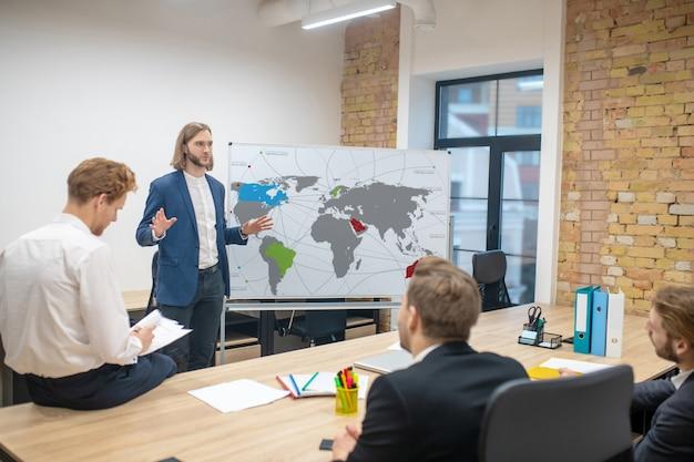 Grupa młodych dorosłych optymistycznych mężczyzn w biurze podczas prezentacji zainteresowanych dobrym nastrojem