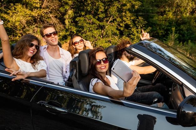Grupa młodych dziewcząt i chłopaków robi selfie w czarnym kabriolecie w ciepły słoneczny dzień. .