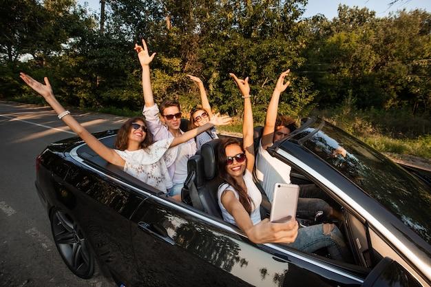 Grupa młodych dziewcząt i chłopaków trzyma ręce i robi selfie w czarnym kabriolecie w słoneczny dzień. .
