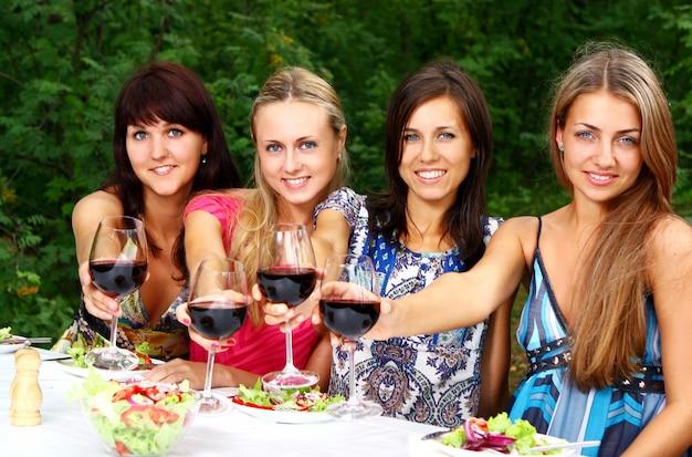 Grupa młodych dziewcząt picia wina w parku