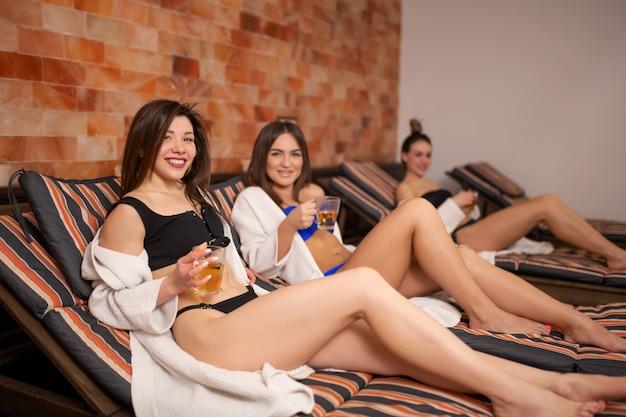 Grupa młodych dziewcząt relaksujących się na drewnianym pokładzie w saunie. zabawy w kobiecej firmie