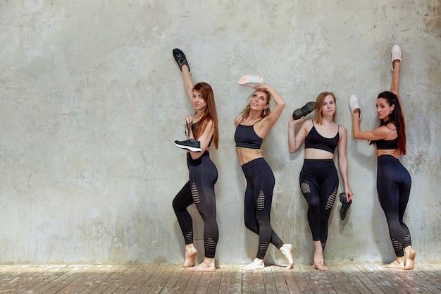 Grupa młodych dziewcząt sportowych odpoczynku po treningu w przestronnym studio na poddaszu.