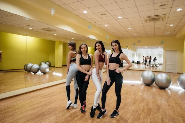 Grupa młodych dziewcząt sportowych pozujących na siłowni po treningu. zdatność. zdrowy tryb życia.