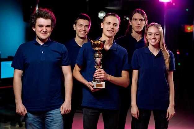 Grupa młodych graczy w niebieskich koszulkach stojących w klubie komputerowym, lider zespołu trzymający złoty puchar, wygrywający w cybersportowych zawodach