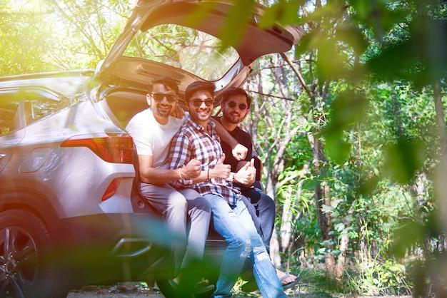 Grupa młodych i atrakcyjnych przyjaciół z indii, azji, siedzących w otwartym bagażniku samochodu podczas letniej wycieczki samochodowej