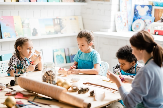 Grupa młodych i sprytnych uczniów wraz z nauczycielem siedzą przy stole i robią papierowe dekoracje na nadchodzące wakacje