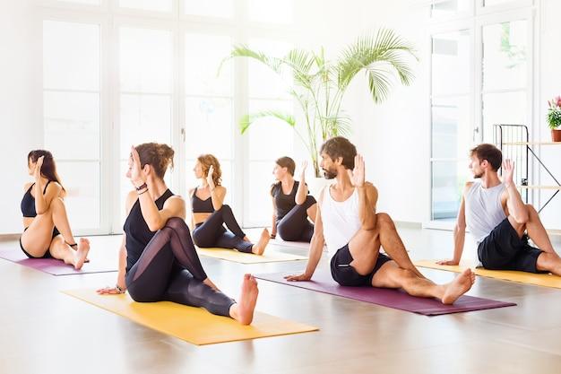 Grupa młodych i wysportowanych ludzi wykonujących matsyendrasana podczas zajęć jogi w przestronnym, jasnym studio