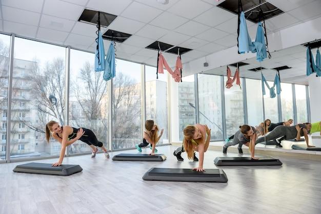 Grupa młodych kobiet ćwiczeń na siłowni