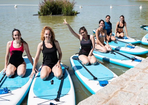 Grupa młodych kobiet w strojach kąpielowych robi joga na jeziorze miasta wczesnym rankiem. zrównoważona pozycja - koncepcja zdrowego życia i naturalnej równowagi między ciałem a rozwojem umysłowym.