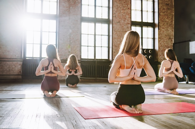 Grupa młodych kobiet wykonuje kompleks rozciągających asan jogi w klasie stylu loft.