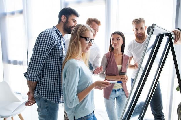 Grupa młodych kolegów ubranych dorywczo stojących razem w nowoczesnym biurze i burzy mózgów