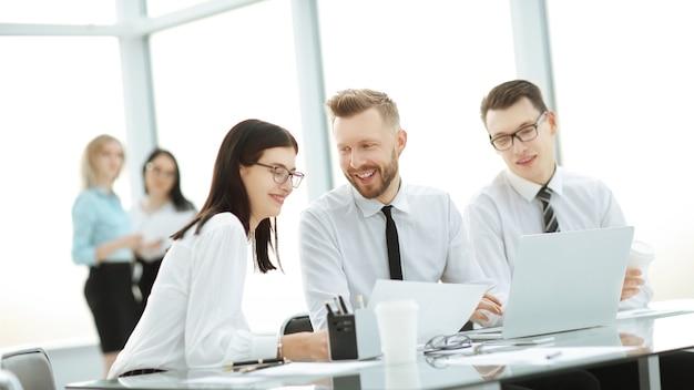 Grupa młodych kolegów za pomocą laptopa w biurze