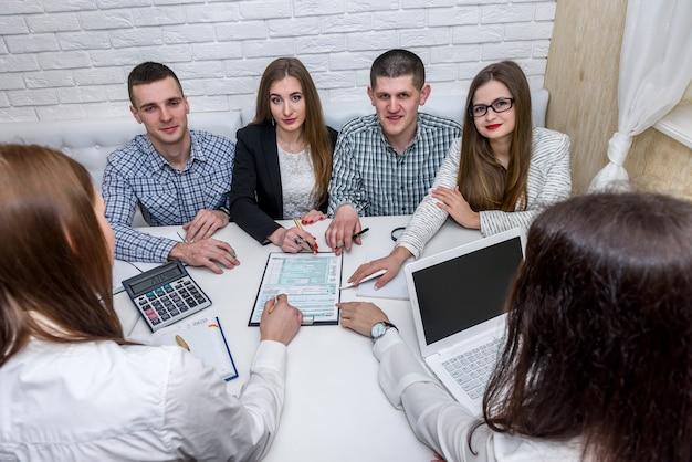 Grupa młodych konsultantów w biurze wskazująca na formularz podatkowy 1040