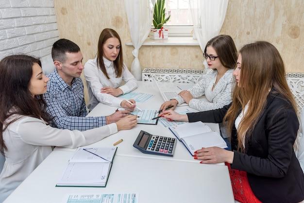 Grupa młodych konsultantów w biurze wskazuje na formularz podatkowy 1040