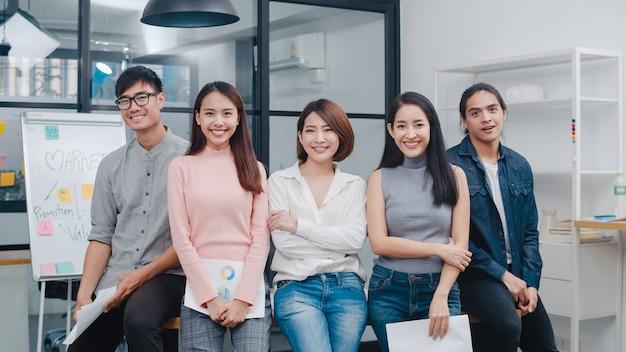 Grupa młodych kreatywnych ludzi z azji w eleganckich ubraniach na co dzień, patrząc na kamerę i uśmiechając się