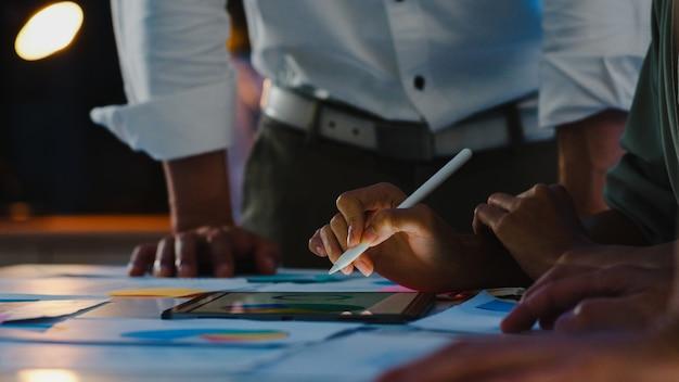 Grupa młodych kreatywnych ludzi z azji w eleganckim stroju casual omawiająca biznesową burzę mózgów