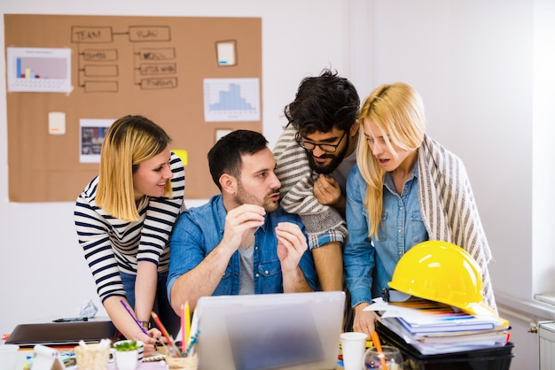 Grupa młodych kreatywnych projektantów stojących nad stołem i rozmawiających o problemach w ich pracy.