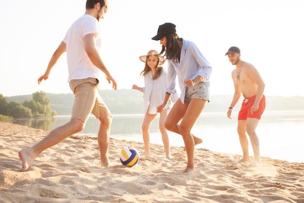 Grupa młodych ludzi bawiących się piłką na plaży. młodzi przyjaciele korzystający z letnich wakacji na piaszczystej plaży.