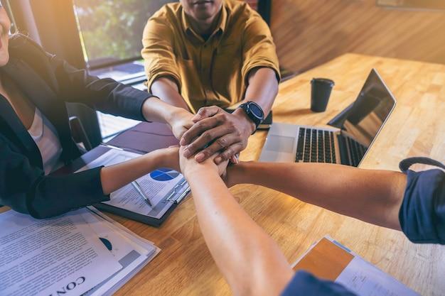 Grupa młodych ludzi biznesu łączy ręce w biurze praca zespołowa dla koncepcji sukcesu