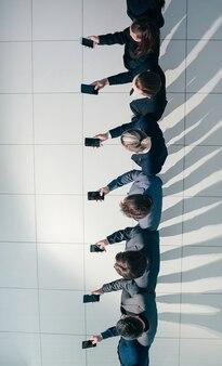 Grupa młodych ludzi biznesu patrzących na ekrany swoich smartfonów