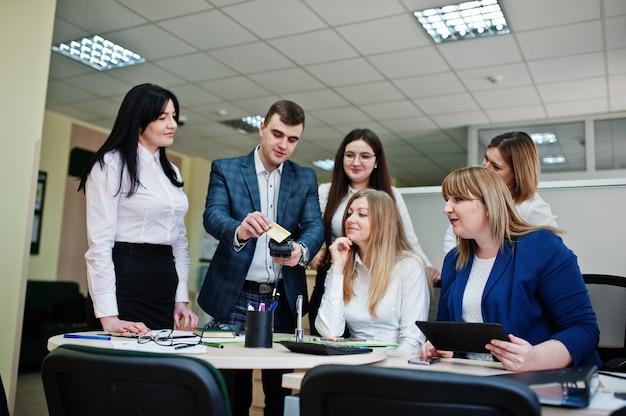 Grupa młodych ludzi biznesu, pracowników banku, spotyka się i pracuje w nowoczesnym biurze. pracuj z kartą kredytową i terminalem pos.