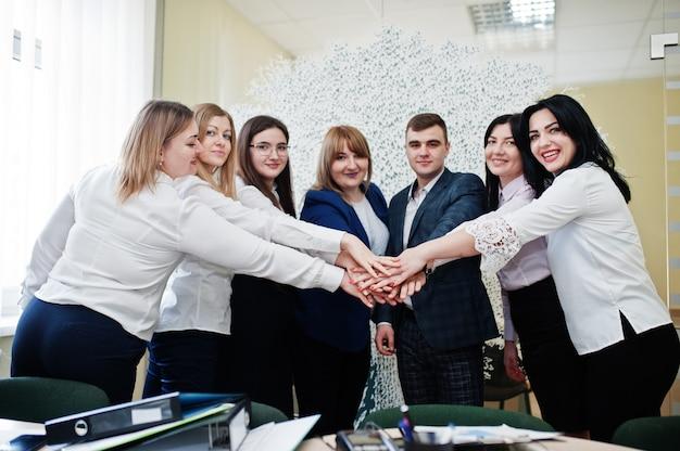 Grupa młodych ludzi biznesu pracowników banku spotykają się i pracują w nowoczesnym biurze ręce do góry.