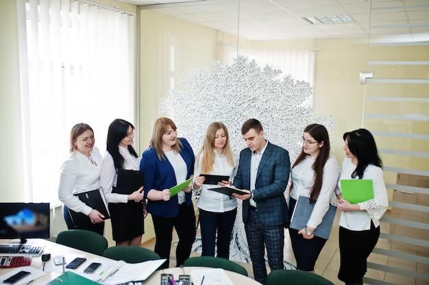 Grupa młodych ludzi biznesu pracowników banku ze schowka mają spotkanie i pracę w nowoczesnym biurze.