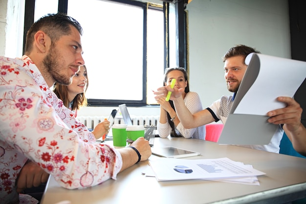 Grupa młodych ludzi biznesu, przedsiębiorców start-upowych pracujących nad swoim przedsięwzięciem w przestrzeni coworkingowej.