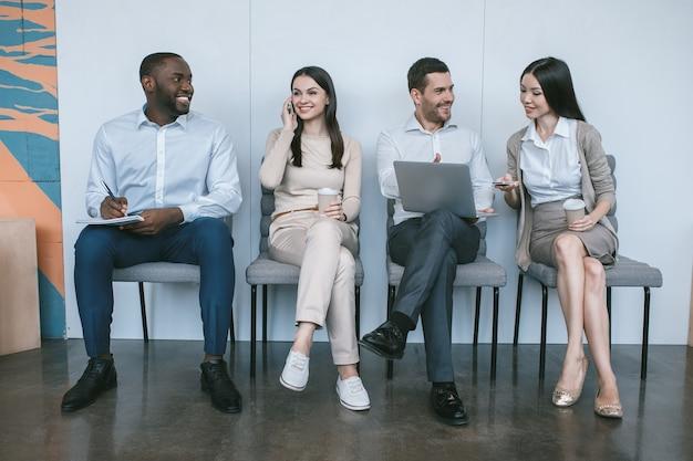 Grupa młodych ludzi biznesu siedzących razem na krzesłach w biurze