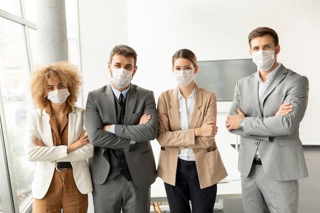 Grupa młodych ludzi biznesu stojących w biurze i noszących maski jako ochrona przed wirusem koronowym
