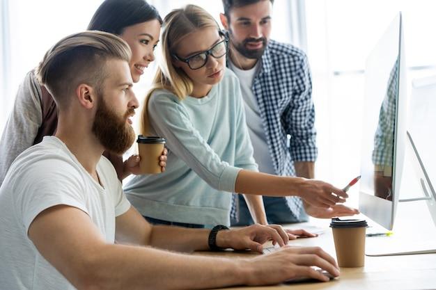 Grupa młodych ludzi biznesu wesoły, pracujących i komunikujących się przy biurku razem