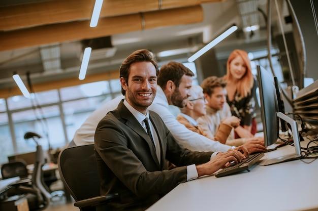 Grupa młodych ludzi biznesu współpracuje z komputerem stacjonarnym
