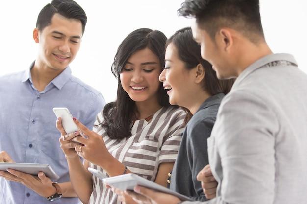 Grupa młodych ludzi biznesu z własnym gadżetem