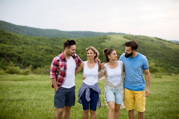 Grupa młodych ludzi chodzących w polu latem