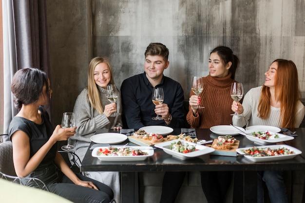Grupa młodych ludzi, ciesząc się razem obiad i wino