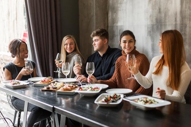 Grupa młodych ludzi, ciesząc się razem obiad