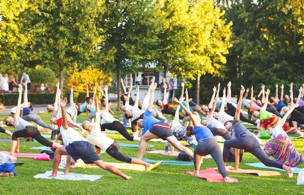 Grupa młodych ludzi ćwiczy jogę w parku o zachodzie słońca.