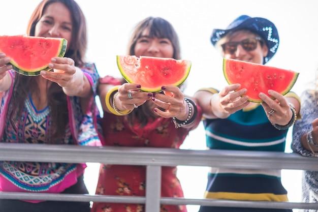 Grupa młodych ludzi kaukaskich kobiet pokazujących czerwony świeży letni arbuz i uśmiech razem w przyjaźni - wakacje i wypoczynek dla przyjaciół - koncepcja zabawy