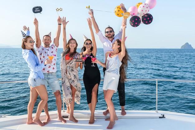 Grupa młodych ludzi obchodzi urodziny podczas rejsu morskiego