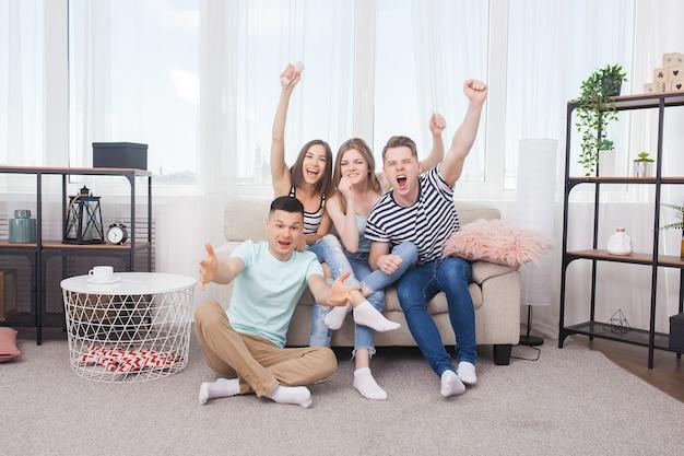 Grupa młodych ludzi ogląda telewizję. aktywna młodzież w domu kibicuje drużynie. wesoły znajomi w pomieszczeniu zabawy razem.