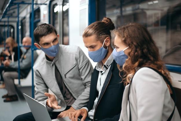 Grupa młodych ludzi omawiających wiadomości online, siedząc w wagonie metra